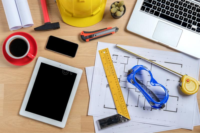 Architectural office desk with laptop. Smart phone,tablet,cup of coffee and engineer equipment.Top view background construcion project idea concept stock photography