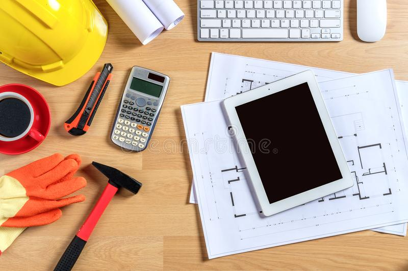 Architectural office desk with laptop. Smart phone,tablet,cup of coffee and engineer equipment.Top view background construcion project idea concept stock image
