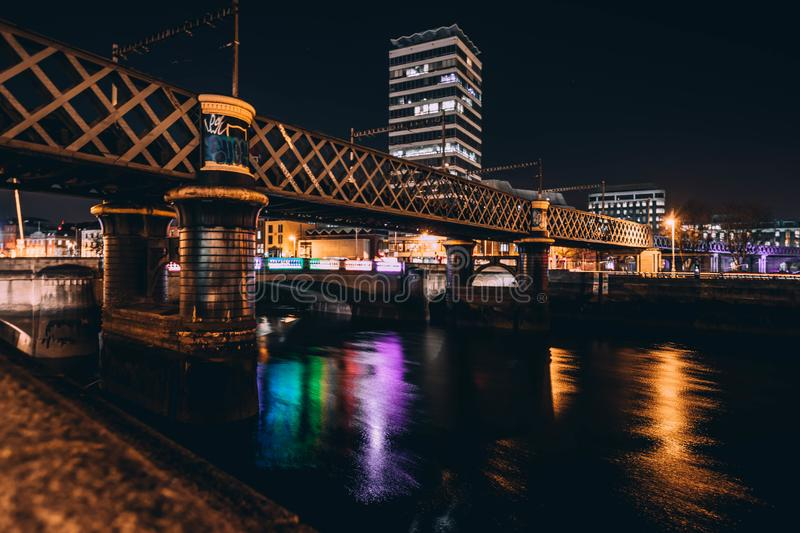 Architectural Photo of Brown Concrete Bridge and High Rise Building during Night Time stock photos