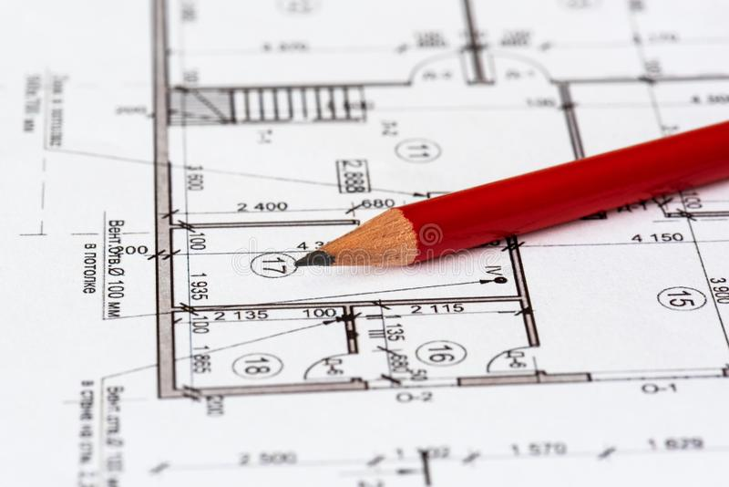 The architectural plan of the house is printed on a white sheet of paper. A red pencil on it. June 2018, Russia, Moscow stock photography