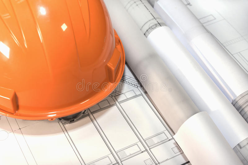 Architectural plans project drawing and blueprints rolls with he. Blueprints rolls and orange helmet over architectural plans project drawing, architect stock photo