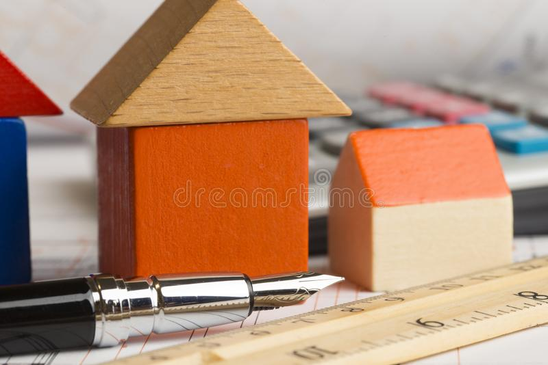 Architectural project of a new house with wooden model house , calculator and plans on the table stock images