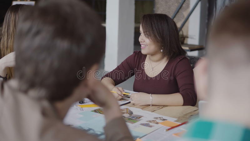 Architectural start-up company. Young creative team working in loft office. African woman talking with group of people. royalty free stock photography