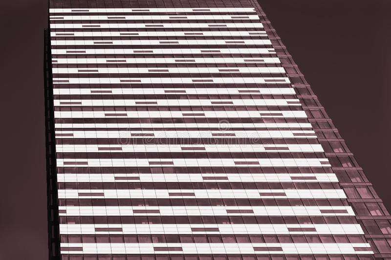 Architectural toned background of modern Iron-concrete wall with windows. Multistory buildings at night. Modern neon royalty free stock images