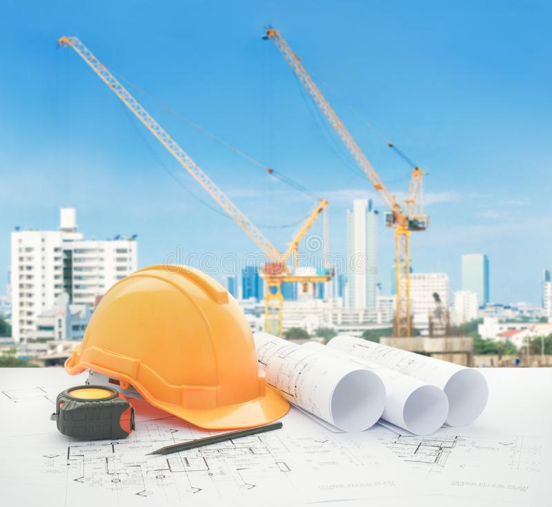 Architecturale blauwdruk met veiligheidshelm en hulpmiddelen over bouwwerf met torenkraan stock afbeeldingen