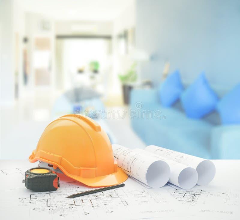 Architecturale blauwdruk met veiligheidshelm en hulpmiddelen over modern woonkamerbinnenland stock foto