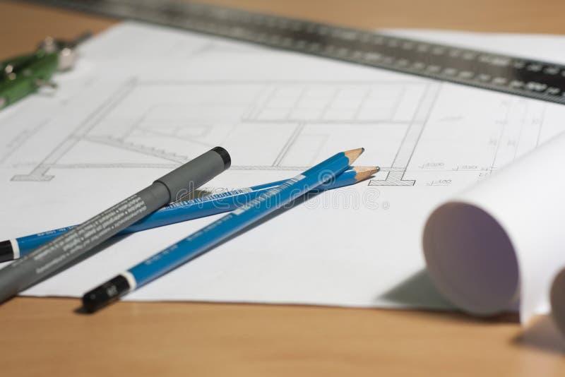 Architecturale blauwdrukken en blauwdrukbroodjes en een tekeningsinstrumenten stock afbeeldingen