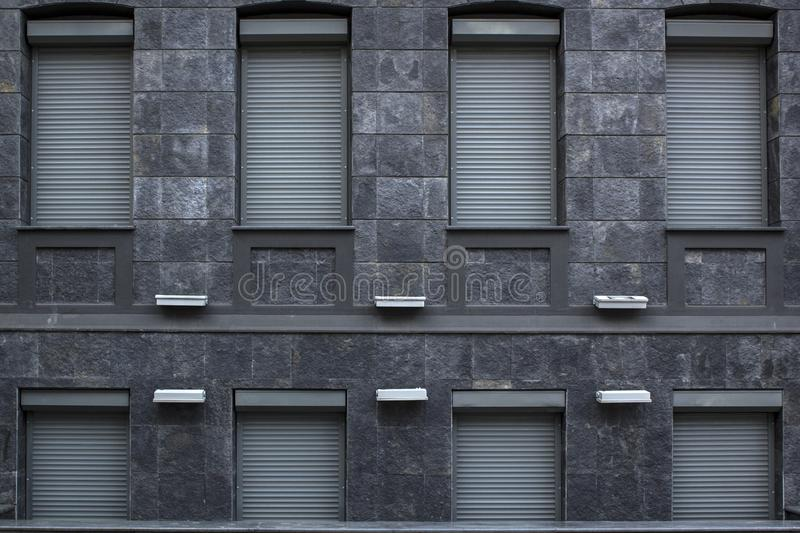 Architecture building fasade from grey granite stone with windows closed with metal rollets stock image