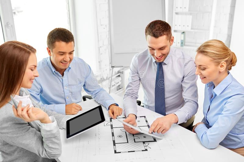 Happy business team discussing blueprint at office royalty free stock photos