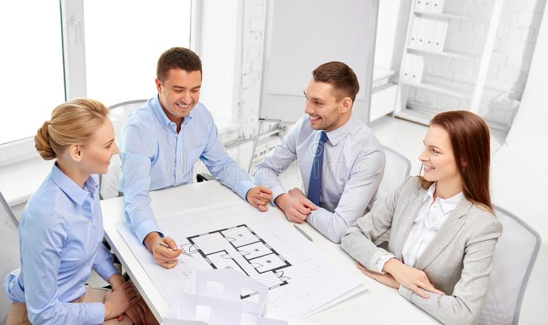 Happy business team discussing blueprint at office royalty free stock photography