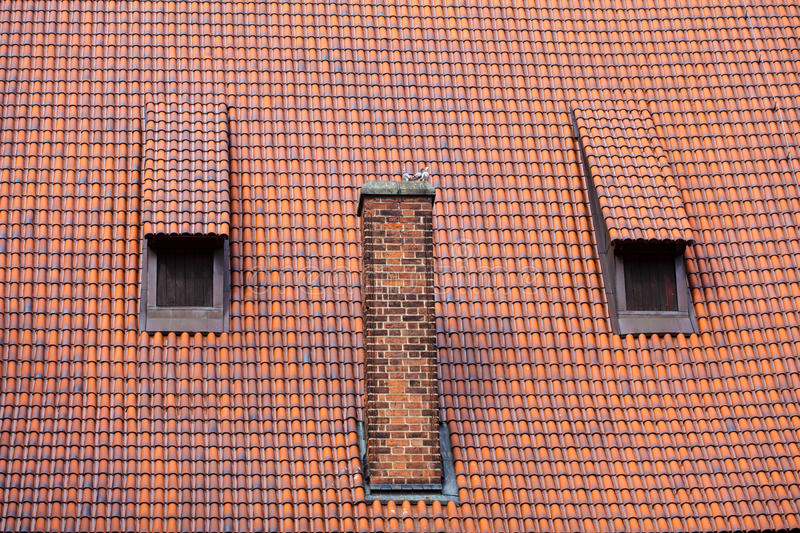 Architecture detail chimney and garret red tiles roof. Architecture detail chimney red tile garret roof with windows old town Gdansk Poland stock photo