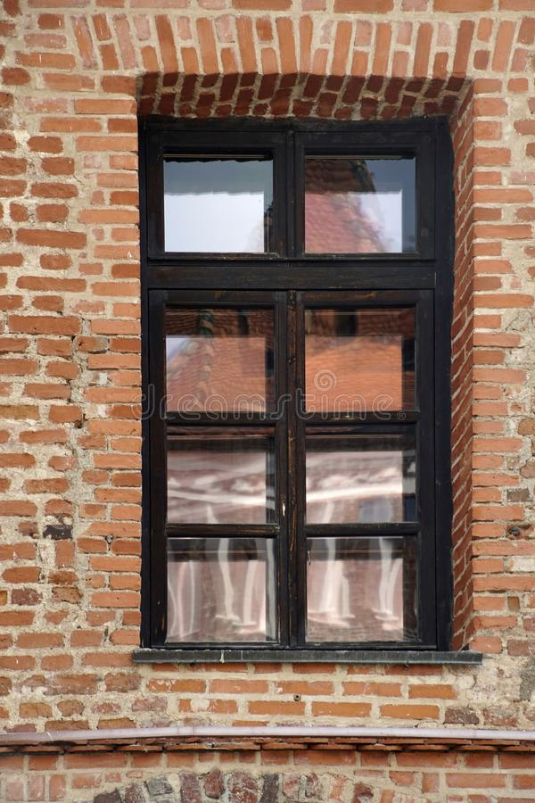Architecture details. Beautiful window in the brick palace castle. The reflection in the glass of the sky and buildings. Brown, texture, facade, city royalty free stock photo