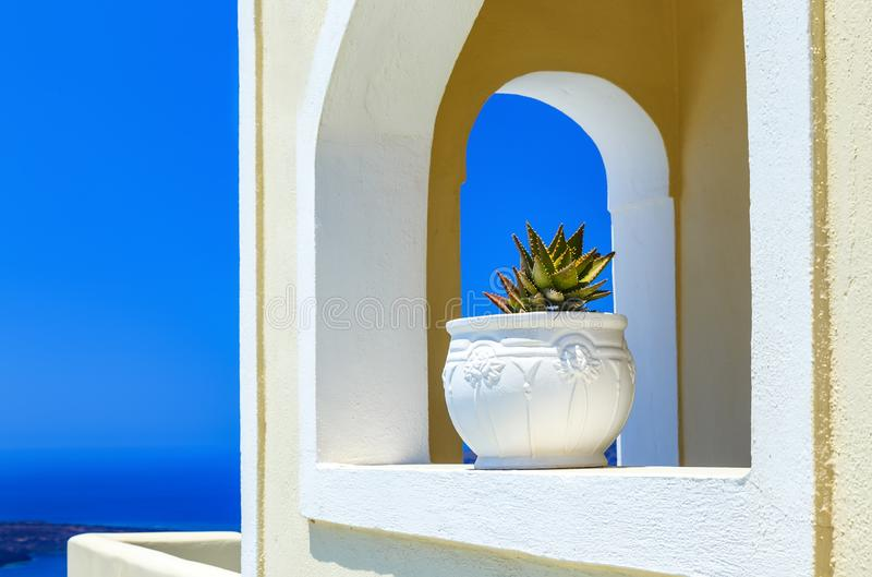 Architecture details of white buildings in Santorini island, Greece. Arched window of traditional house with flower in pot with ancient design. Blue sky royalty free stock image