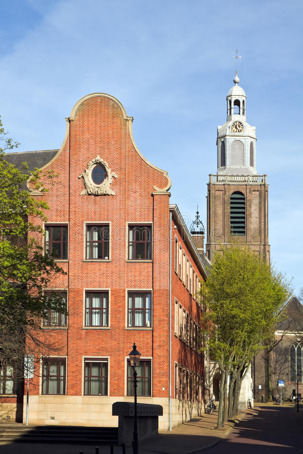 Architecture with Dutch gable. Architectural detail - part of town hall or city hall with Dutch gable and old church in background royalty free stock photo