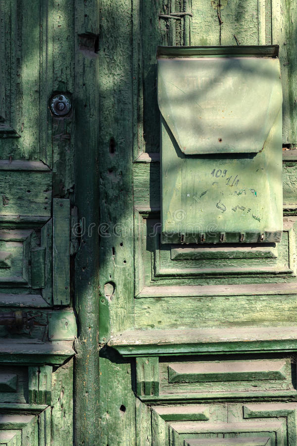 Architecture element. An old green wooden door with a mailbox. An old green wooden door with a mailbox royalty free stock photos