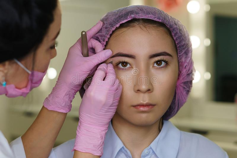 Architecture of eyebrows. Microbleeding eyebrow measurement. Microbleeding and eyebrow architecture. Beautician shapes beauty of girl`s eyebrows. Cosmetic royalty free stock image