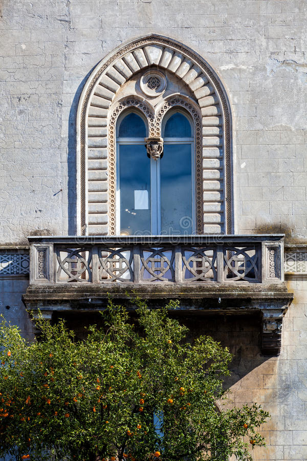 Architecture, historic arched window with balcony. Tree of oranges. royalty free stock photography
