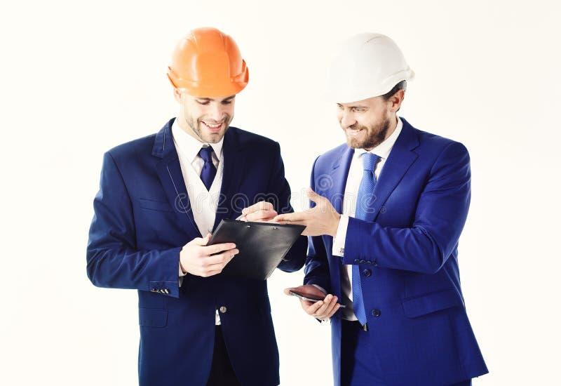 Architecture, ingénierie, concept de succès Ingénieurs avec des barbes et des visages heureux Regard d'associés au bâtiment images libres de droits