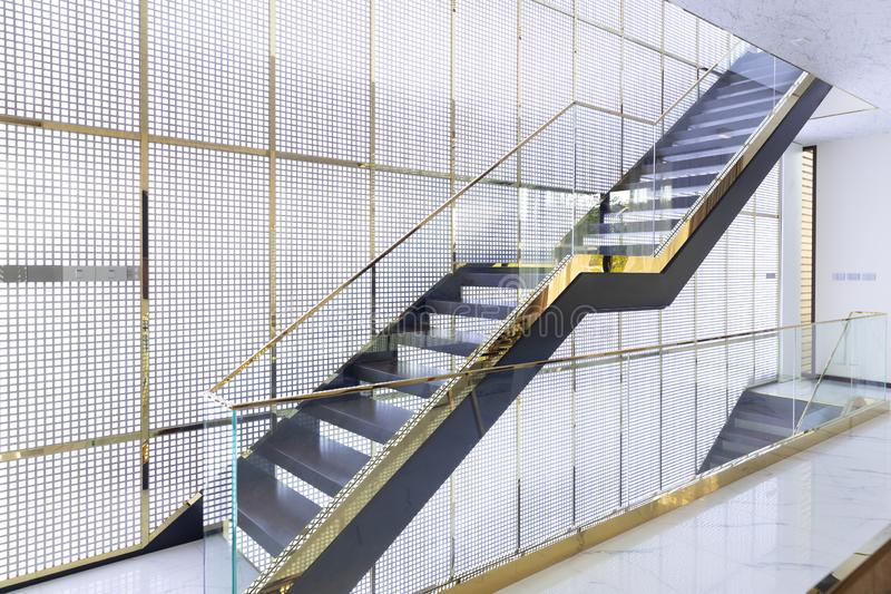 Luxury wooden staircase with glass railing and gold handrail in golden grille house interior stock images