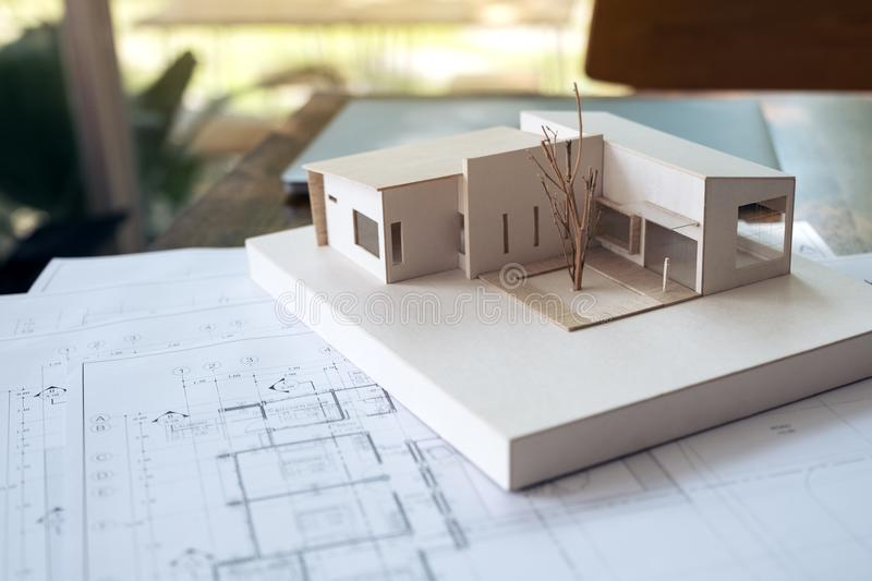 An architecture model with shop drawing paper and laptop on table in office with blur nature. Background stock photos
