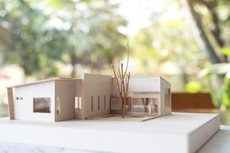 An architecture model with shop drawing paper on table in office with blur nature stock photography