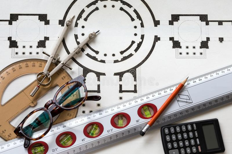 Project architecture with an old historic plan and useful tools. Architecture project with an old historic plan with compass, rules, goniometer,calculator and royalty free illustration