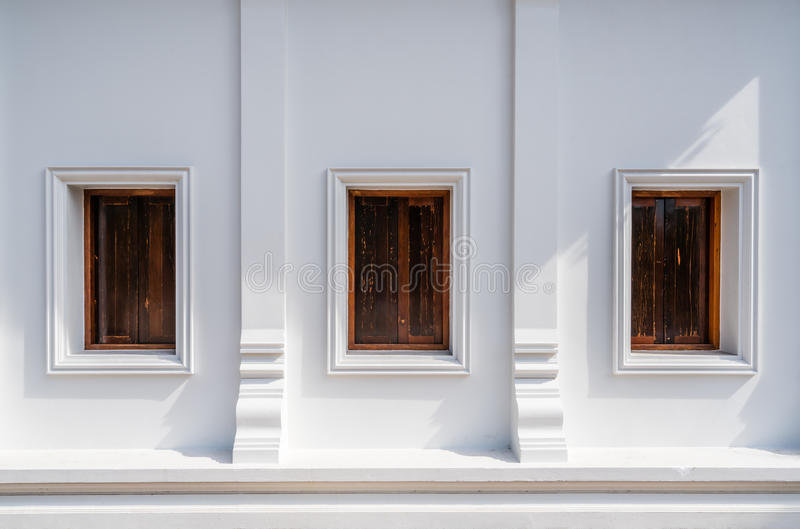 Architecture of Thailand's public temple's wall with three wooden windows stock photography