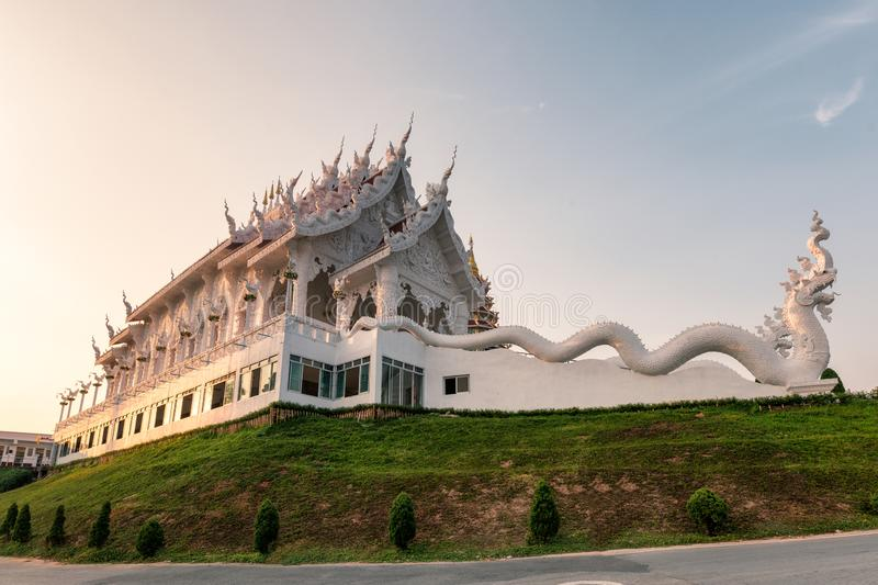 Architecture white church with dragon statue on hill in evening at Wat Huay Pla Kang stock image