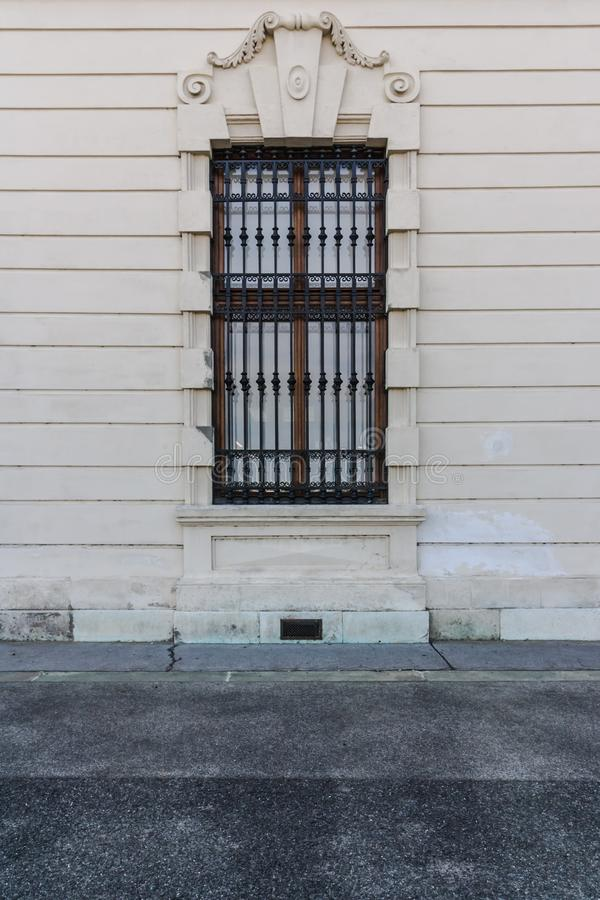 Architecture and windows of ancient renaissance style classical building. Amazing old-style wooden window with wrought-iron black bars. stone framing with royalty free stock photo