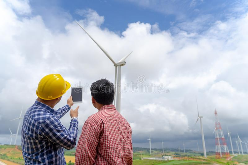 Architecture working with partner at windmill farm. royalty free stock images