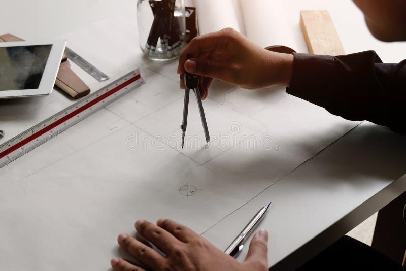 Architectuur die op blauwdrukdocument trekken met verdelers op handen stock fotografie