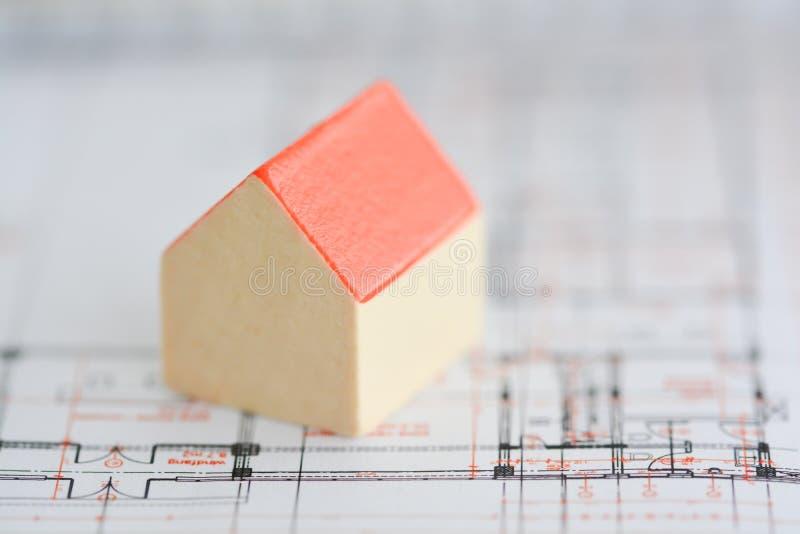 Architectuurplannen van een gebouw met klein modelhuis bovenop blauwdrukken royalty-vrije stock foto's