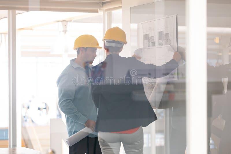 Architekci dyskutuje nad projektem na szkło desce zdjęcie stock