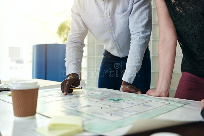 Architekci dyskutuje projekty wpólnie przy stołem w biurze obraz stock