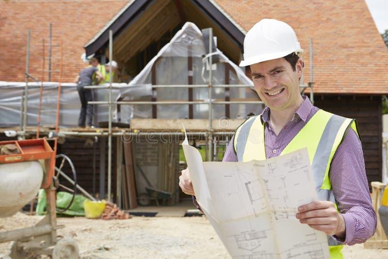 Architekt On Building Site, das Haus-Pläne betrachtet stockfotos