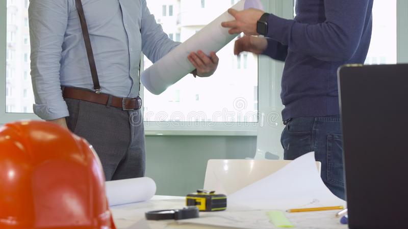 Architekt daje rolce budynków plany jego kolega zdjęcia royalty free