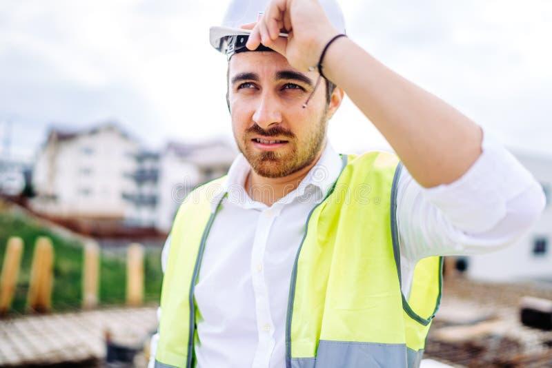 Architekt, der an Baustelle, tragendem Schutzhelm und Sicherheitsweste arbeitet lizenzfreies stockfoto