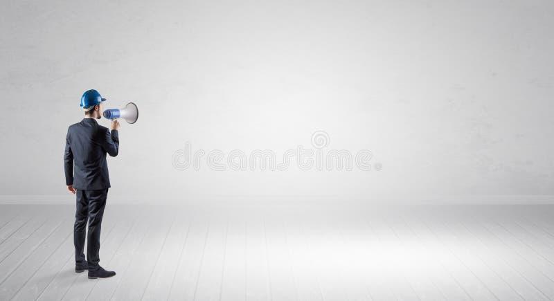 Architekt, der in einem leeren Raum steht und einen Plan h?lt lizenzfreies stockbild