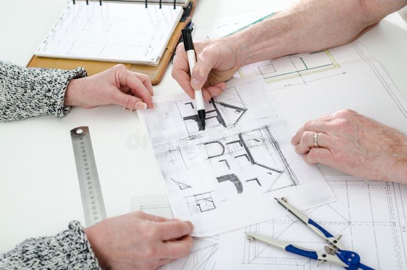 Architekt, der Hauspläne zeigt lizenzfreie stockfotos