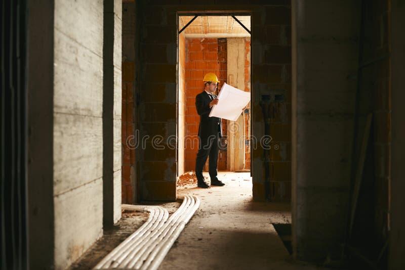Architekt, der im Bau im Haus mit dem Aufbau von Winkel des Leistungshebels steht stockfotos