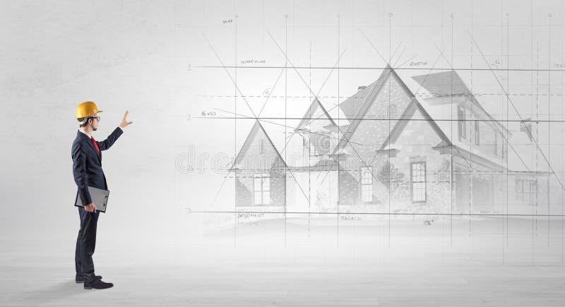 Architekt, der mit Hausplan steht stockfotografie
