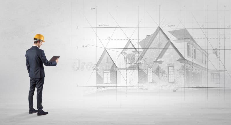 Architekt, der mit Hausplan steht stockfotos