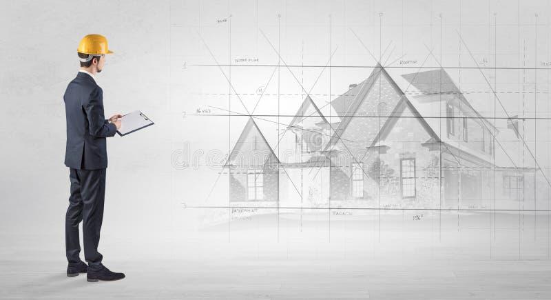 Architekt, der mit Hausplan steht stockfoto