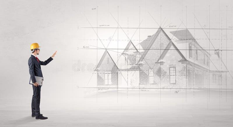 Architekt, der mit Hausplan steht lizenzfreies stockbild