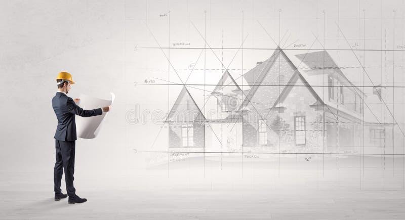 Architekt, der mit Hausplan steht stockbilder