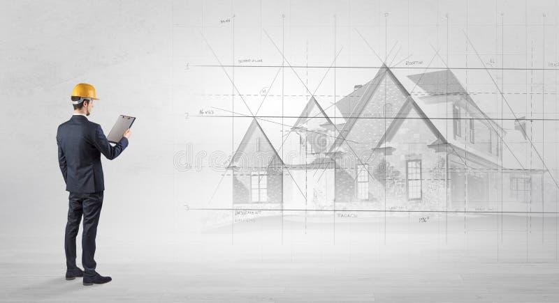 Architekt, der mit Hausplan steht lizenzfreie stockfotos