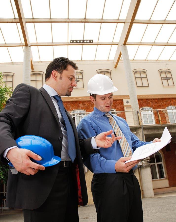 Architekt, der mit Investor über den Lichtpausen spricht lizenzfreies stockfoto