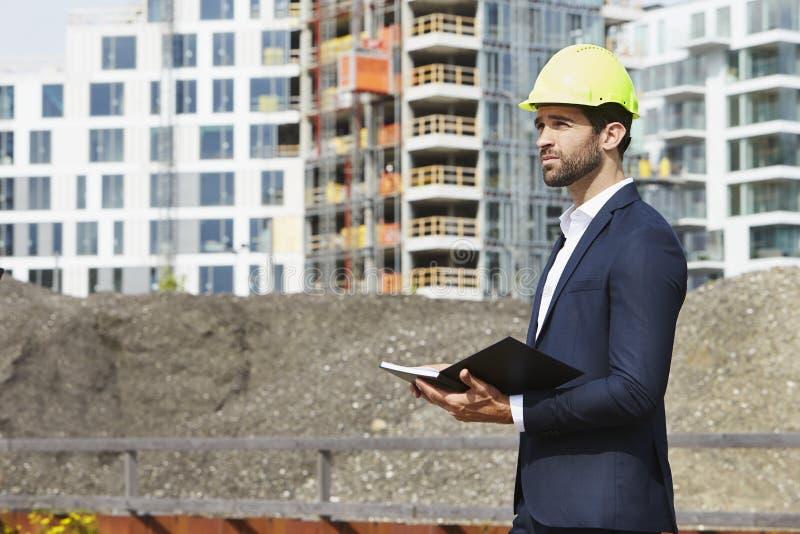 Architekt, der Plan auf Baustelle macht stockbilder