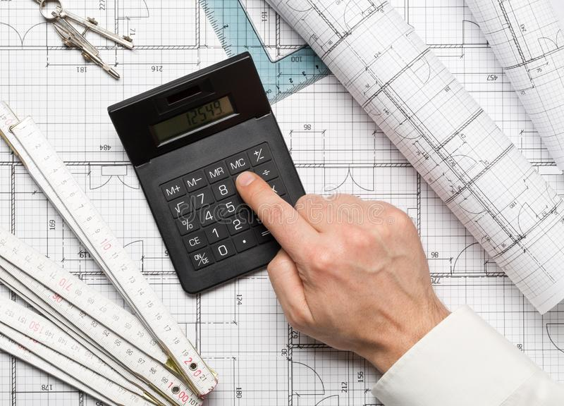 Architekt, der Taschenrechner auf Architekturplanwohnungsbauplan mit Bleistift, Machthaber, Kompasssen und quadratischem flatlay  stockbilder