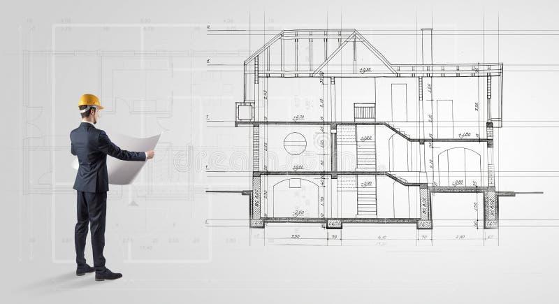 Architekt, der zu einem Hausplan schaut lizenzfreies stockbild